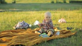 Śliczny chłopiec obsiadanie na koc w parku Dziecko less niż on i rok bawić się zbiory wideo