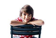 Śliczny chłopiec obsiadanie na krześle ono uśmiecha się, odizolowywający fotografia royalty free
