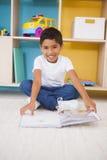 Śliczny chłopiec obsiadanie na podłogowym czytaniu w sala lekcyjnej obrazy royalty free