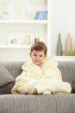 Śliczny chłopiec obsiadanie w bathrobe kanapie w domu fotografia royalty free