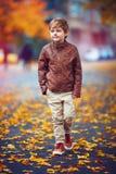 Śliczny chłopiec odprowadzenie przez jesieni miasta ulicy Obraz Royalty Free