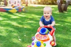 Śliczny chłopiec uczenie chodzić z piechur zabawką na zielonej trawy gazonie przy podwórkem Dziecko śmia się zabawę robi pierwsze obrazy royalty free