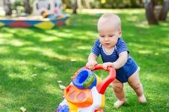 Śliczny chłopiec uczenie chodzić z piechur zabawką na zielonej trawy gazonie przy podwórkem Dziecko śmia się zabawę robi pierwsze obraz stock