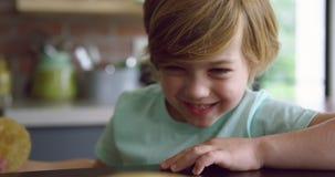 Śliczny chłopiec zrywania blin od talerza przy łomotać stół w kuchni 4k w domu zdjęcie wideo