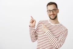Śliczny czuły dorosłej samiec homoseksualisty model w szkłach wskazuje przy górnym lewym kątem z palca pistoletem i ono uśmiecha  obrazy royalty free