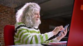Śliczny dojrzały caucasian mężczyzna z wielką białą brodą i włosy swiping jego telefon podczas gdy siedzący obok laptopu w cegle