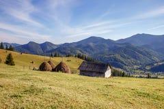 Śliczny drewniany dom i przeprowadza żniwa na góry tle Zdjęcia Royalty Free
