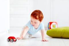 Śliczny dziecięcy dziecko bawić się z drewnianym zabawkarskim samochodem w domu Zdjęcie Royalty Free