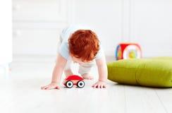 Śliczny dziecięcy dziecko bawić się z drewnianym zabawkarskim samochodem w domu Fotografia Stock