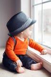 Śliczny dziecięcy dziecko w kapeluszowym pobliskim okno Fotografia Stock
