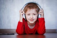 Śliczny dzieciak słucha muzyka na hełmofonach i cieszyć się obraz royalty free