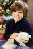 Śliczny dzieciak trzyma małego szczeniaka psa ono uśmiecha się przed choinka środka strzałem Fotografia Stock