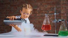 Śliczny dziecko badacz prowadzi eksperyment z ciekłym azotem zdjęcie stock