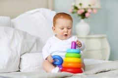 Śliczny dziecko bawić się z kolorowym tęczy zabawki ostrosłupa obsiadaniem na łóżku w białej pogodnej sypialni Zabawki dla małych Fotografia Royalty Free