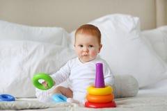 Śliczny dziecko bawić się z kolorowym tęczy zabawki ostrosłupa obsiadaniem na łóżku w białej pogodnej sypialni Zabawki dla małych Fotografia Stock