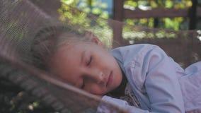 Śliczny dziecko dziewczyny lying on the beach na hamaku i relaksuje przy ogródem zdjęcie wideo