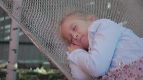 Śliczny dziecko dziewczyny lying on the beach na hamaku i relaksuje przy ogródem zbiory wideo
