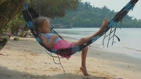 Śliczny dziecko dziewczyny lying on the beach na hamaku i relaksuje przy piaskowatą plażą w zwolnionym tempie zbiory wideo