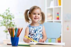 Śliczny dziecko dziewczyny rysunek z colourful ołówkami Zdjęcia Stock