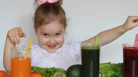 Śliczny dziecko je zielonych liście sałata Dziecko dziewczyna pije jarzynowych smoothies marchewka, burak i zieleń -, zbiory wideo