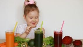 Śliczny dziecko je zielonych liście sałata Dziecko dziewczyna pije jarzynowych smoothies marchewka, burak i zieleń -, zbiory