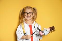 Śliczny dziecko ono wyobraża sobie jak lekarka podczas gdy bawić się z odruch lalą i młotem fotografia royalty free