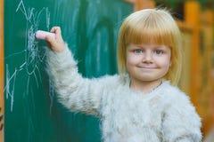 Śliczny dziecko rysunek z kredą na blackboard plenerowym Obraz Stock