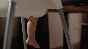 Śliczny dziecko siedzi na wysokości dzieci krześle i rusza się jego nogi Dzieci dźwignięcia jeden noga zbiory