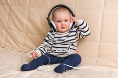 Śliczny dziecko z hełmofonami słucha muzyka w domu zdjęcie royalty free