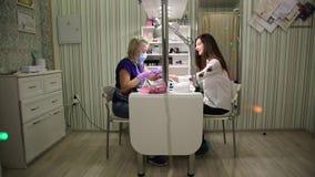 Śliczny dziewczyna mistrz robi manicure'owi zbiory