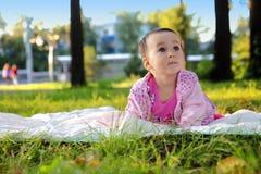 Śliczny dziewczynki lying on the beach na trawie w parku zdjęcie stock
