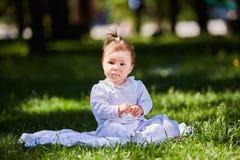 Śliczny dziewczynki obsiadanie na zielonej trawie w miasto parku przy ciepłym letnim dniem Obraz Stock