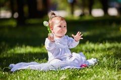 Śliczny dziewczynki obsiadanie na zielonej trawie w miasto parku przy ciepłym letnim dniem Obrazy Stock