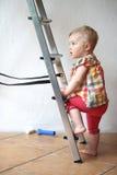 Śliczny dziewczynki pięcie na krok drabinie indoors Zdjęcie Stock
