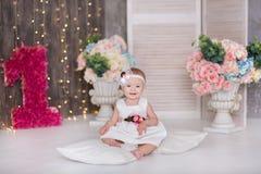 Śliczny dziewczynki 1-2 roczniaka obsiadanie na podłoga z menchiami szybko się zwiększać w pokoju nad bielem odosobniony amerykan Obraz Stock