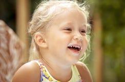 Śliczny dziewczyny dziecko z jogurt ocenami na ona twarz na kolorowym plecy fotografia stock