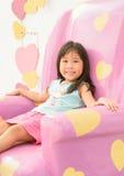 Śliczny dziewczyny obsiadanie relaksuje na różowej kanapie Fotografia Royalty Free
