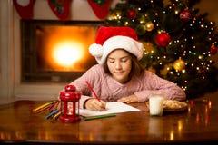 Śliczny dziewczyny writing list Santa przy żywym pokojem Zdjęcia Royalty Free