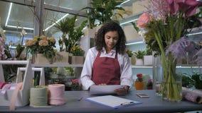 Śliczny flowergirl akceptuje rozkazy w florystycznym sklepie zbiory wideo