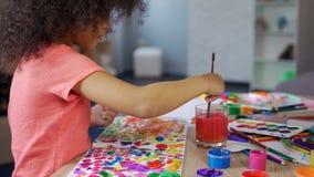 Śliczny kędzierzawy amerykanin afrykańskiego pochodzenia dziewczyny kładzenia paintbrush w wodę, wolny czas zdjęcie royalty free