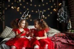 Śliczny kędzierzawy bliźniak dziewczyny obsiadanie na łóżku w dekorującym xmas pokoju na Bożenarodzeniowym wieczór 2018 blisko no Obrazy Stock