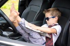 Śliczny kierowca czyta gazetę w samochodzie fotografia royalty free