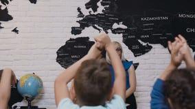 Śliczny kobieta nauczyciel w szkłach podczas czek wiedzy jego ucznie które podnoszą ich ręki up i lekci Dzieci zbiory
