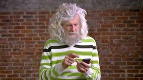 Śliczny kosmaty biały brodaty stary człowiek scrolling jego telefon pozycję i patrzeje kamerę z zrelaksowaną roześmianą twarzą