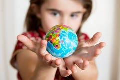 Śliczny lgirl trzyma małą Światową kulę ziemską na ona ręki Obrazy Stock
