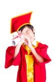 Śliczny Little Boy Jest ubranym Czerwonego toga dzieciaka skalowanie Z Mortarboard Obrazy Stock