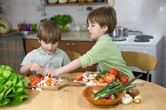 Śliczny Little Boy Pomaga Jego brat bliźniak Robić Świeżej sałatki przy Kuchennym stołem Fotografia Royalty Free