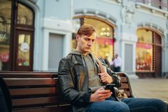 Śliczny mężczyzna siedzi na ławce i używa telefon zdjęcia royalty free