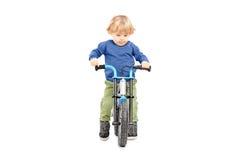 Śliczny męski dzieciak jedzie jego bicykl Zdjęcia Royalty Free
