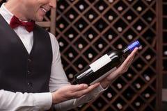 Śliczny męski kelner wybiera perfect napój Zdjęcie Stock